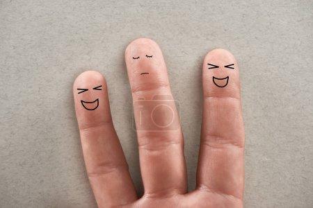 Photo pour Vue partielle de l'homme montrant trois doigts symbolisant les agresseurs rieurs et la triste victime sur fond gris - image libre de droit