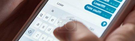 Foto de Foto panorámica de los mensajes ofensivos de escribir abusador mientras se utiliza el teléfono inteligente, editorial ilustrativa - Imagen libre de derechos