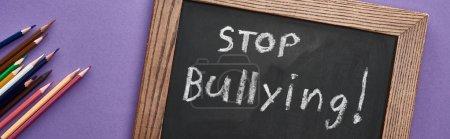 Foto de Foto panorámica de pizarra en marco de madera con stop bullying letras cerca de lápices de colores sobre fondo púrpura - Imagen libre de derechos