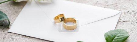 panoramic shot of golden rings on white envelope near roses on grey textured