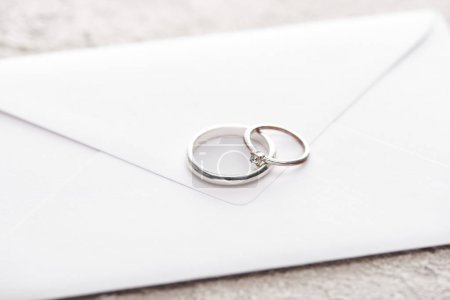 Photo pour Silver wedding rings on white envelope on grey textured surface - image libre de droit