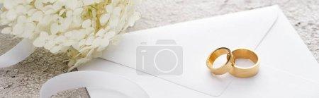 panoramic shot of golden rings on envelope near white ribbon and Hortense flower on grey textured surface
