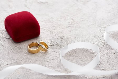 golden rings near red gift box and white ribbon on textured surface