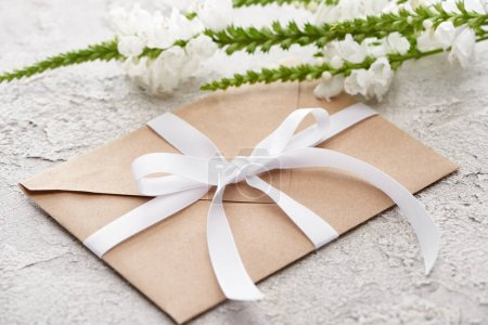 Photo for Beige envelope with white ribbon near flowers on grey textured surface - Royalty Free Image