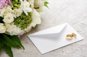 "Постер, картина, фотообои ""wedding rings on white envelope near bouquet of flowers on textured surface """