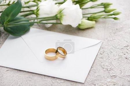 golden wedding rings on envelope near white eustoma flowers on textured surface