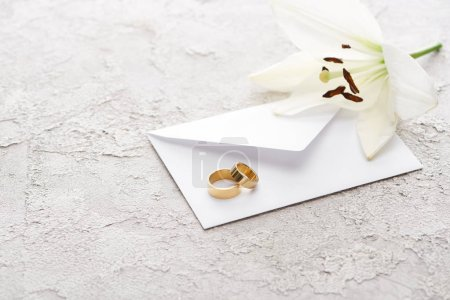 two golden wedding rings on envelope near white lily on textured surface