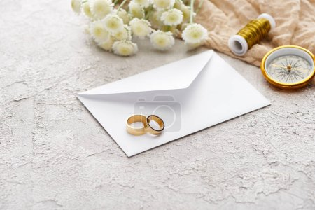 wedding rings on white envelope near chrysanthemums, beige sackcloth, spool and golden compass on textured surface
