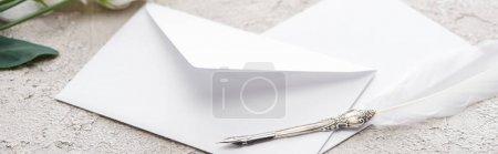 Photo pour Coup panoramique d'enveloppes et stylo plume sur la surface texturée grise - image libre de droit