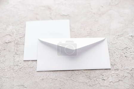 Foto de Sobre de papel blanco y tarjeta en superficie con textura gris - Imagen libre de derechos