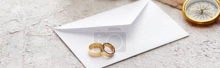 Photo pour Plan panoramique d'anneaux dorés sur enveloppe blanche et boussole sur surface texturée - image libre de droit