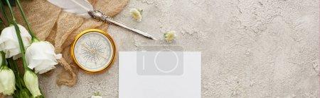 Photo pour Plan panoramique de plume sur sac beige près de la carte blanche, boussole dorée et fleurs d'eustomes sur surface texturée grise - image libre de droit