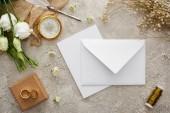 """Постер, картина, фотообои """"верхний вид белого конверта и карты возле бежевого мешка, компаса, золотых колец на подарочной коробке и белых цветов на серой текстурной поверхности"""""""