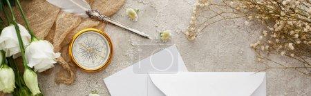 Photo pour Plan panoramique de plume sur sac beige près enveloppe blanche, boussole dorée et fleurs blanches sur surface texturée grise - image libre de droit