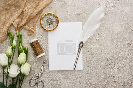 Federkiel auf Blankokarte in der Nähe von goldenem Kompass, beigem Sacktuch, Spule, Schere und weißen Eustoma-Blüten auf grau strukturierter Oberfläche