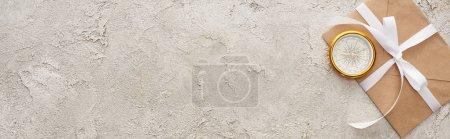 Photo pour Plan panoramique de boussole dorée et enveloppe avec ruban blanc sur surface texturée - image libre de droit