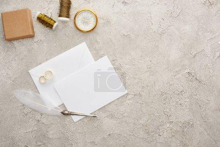 Foto de Top view of golden rings near white empty card, quill pen, spools, compass and gift box on textured surface - Imagen libre de derechos