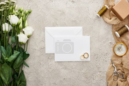 Foto de Top view of pair of wedding rings on empty card, eustoma flowers, gift box, compass, scissors and bobbins on beige sackcloth on textured surface - Imagen libre de derechos