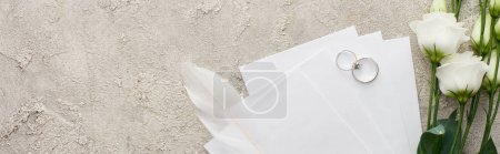 Photo for Panoramic shot of silver rings on invitation cards near white eustoma flowers on textured surface - Royalty Free Image