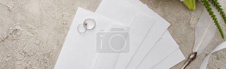 Foto de Foto panorámica de anillos de boda en sobres cerca de pluma de pluma en superficie texturizada - Imagen libre de derechos