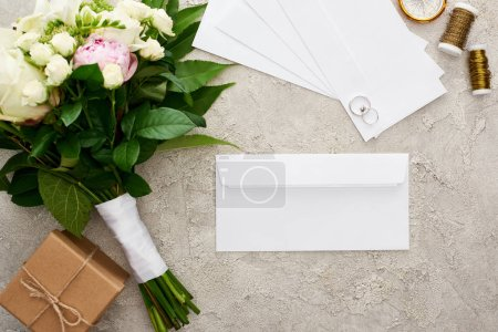 Foto de Top view of white envelopes near wedding rings, gift box, bouquet, bobbins and golden compass on textured surface - Imagen libre de derechos