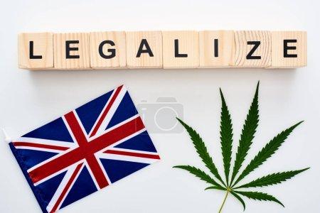 Photo pour Vue supérieure de la feuille de cannabis et légaliser le lettrage sur des cubes en bois près du drapeau de la Grande-Bretagne sur le fond blanc - image libre de droit