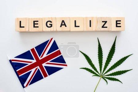 Photo pour Vue supérieure de la feuille verte de cannabis et légalisez le lettrage sur des cubes en bois près du drapeau de la Grande-Bretagne sur le fond blanc - image libre de droit