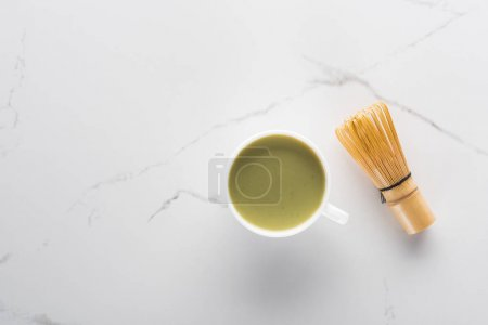 Photo for Top view of cup with green matcha tea and whisk on white table - Royalty Free Image
