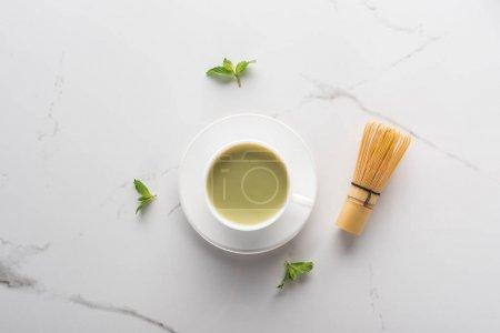 Photo pour Vue du dessus du thé matcha à la menthe sur table blanche - image libre de droit