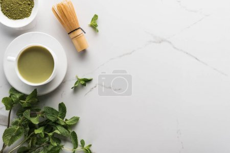 Photo for Top view of green matcha tea mint and whisk on white table - Royalty Free Image