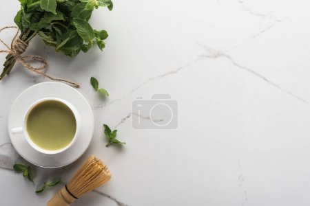 Photo for Top view of traditional matcha tea with mint on white table - Royalty Free Image