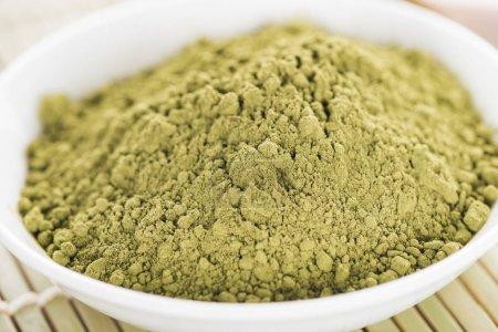 Photo for Close up of matcha green tea powder in bowl on bamboo mat - Royalty Free Image