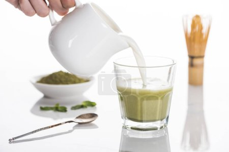 Photo for Cropped view of woman pouring milk into matcha matcha tea on table with whisk and powder - Royalty Free Image