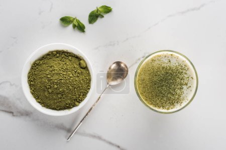 Photo for Top view of matcha tea powder and drink in glass on white table - Royalty Free Image