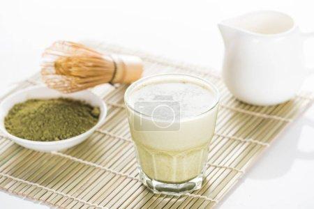 Photo pour Thé vert de matcha avec du lait sur le tapis de bambou - image libre de droit