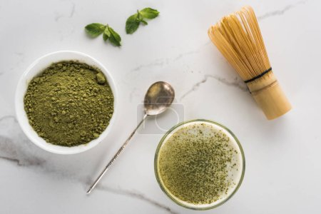 Photo for Top view of green matcha tea powder and drink in glass on white table - Royalty Free Image