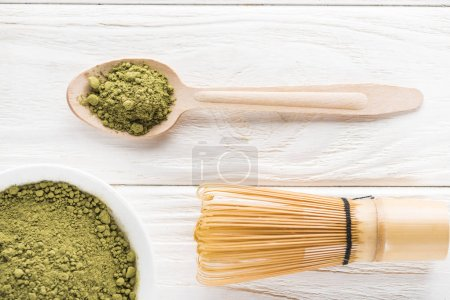 Photo for Top view of wooden spoon with powder of green matcha tea and whisk - Royalty Free Image