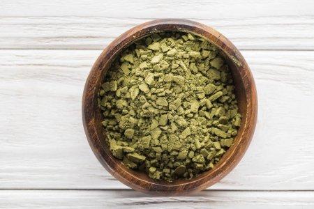 Photo pour Vue du dessus d'un bol en bois avec de la poudre de thé matcha vert sur table blanche - image libre de droit