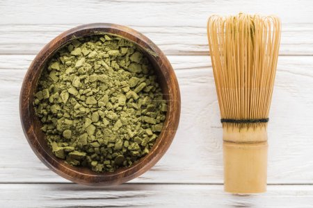 Photo for Top view of wooden bowl with powder of green matcha tea on white table with whisk - Royalty Free Image
