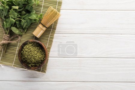 Photo for Top view of green matcha tea powder and mint on bamboo mat on white table - Royalty Free Image