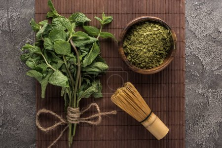 Photo for Top view of green matcha tea powder, mint and whisk on bamboo mat on dark stone table - Royalty Free Image