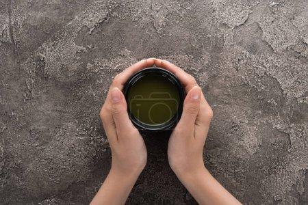 Photo pour Vue supérieure de la femme retenant le thé de matcha de matcha dans des mains - image libre de droit
