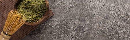 Photo pour Vue du dessus de la poudre de thé vert matcha dans un bol avec fouet sur tapis de bambou sur table en pierre sombre - image libre de droit