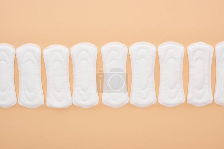 Photo for Flat lay with white cotton sanitary towels isolated on beige - Royalty Free Image