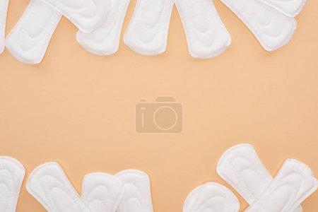 Photo pour Vue de dessus des serviettes hygiéniques dispersées en coton blanc isolées sur beige - image libre de droit