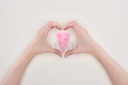 Photo pour Vue recadrée de femme affichant le signe de coeur avec des mains autour de la tasse menstruelle en plastique rose d'isolement sur le gris - image libre de droit