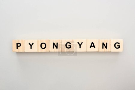 Photo pour Vue de dessus des blocs de bois avec lettrage Pyongyang sur fond blanc - image libre de droit