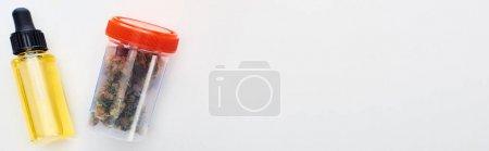 Photo pour Vue supérieure du cannabis dans le récipient en plastique près de l'huile de cbd dans la bouteille sur le fond blanc, projectile panoramique - image libre de droit