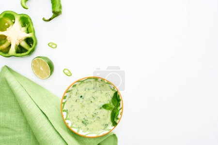Photo for Top view of delicious creamy green vegetable soup served with napkin isolated on white - Royalty Free Image