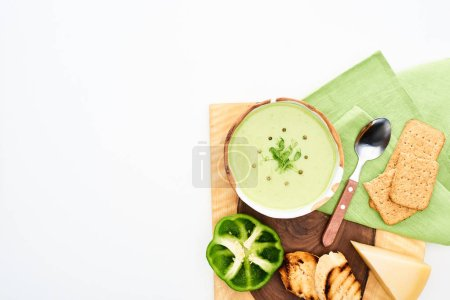 Photo for Top view of delicious creamy green vegetable soup served on wooden cutting board with croutons and cheese isolated on white - Royalty Free Image